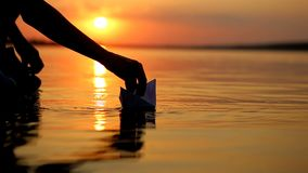 Boy Launching Paper Boat. Little boy launching paper boat on water from beach stock video footage