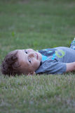 Boy on lawn. Happy Young toddler boy lying on grass in summer Stock Images