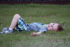 Boy on lawn. Happy Young toddler boy lying on grass in summer Stock Photos