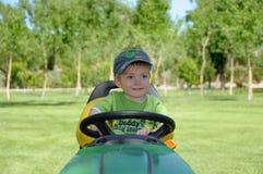 Boy on lawnmower. Smiling boy sat on lawnmower in summer Stock Image
