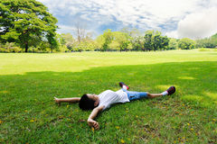 Boy lay on the grass feel relax. Asian Boy lay on the grass feel relax royalty free stock image