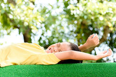 Boy lay on the green lawn Stock Images