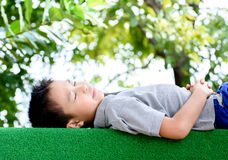 Boy lay on the green lawn Stock Image