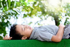 Boy lay on the green lawn Stock Photos