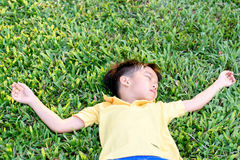 Boy lay on the green lawn Royalty Free Stock Photography