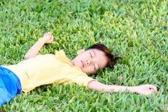 Boy lay on the green lawn Stock Photos