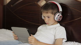 The boy lay listening to music or have an e-learning class using his tablet computer that is connected to a pair of stock footage