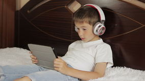 The boy lay listening to music or have an e-learning class using his tablet computer that is connected to a pair of stock video footage
