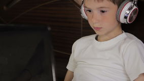 The boy lay listening to music or have an e-learning class using his tablet computer that is connected to a pair of stock video