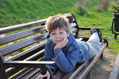 The boy lay on a park bench Royalty Free Stock Image