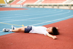 Boy lay on the running track Stock Images