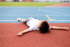 Boy lay on the running track Royalty Free Stock Images
