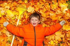 Boy laying on the autumn leaves with rake Stock Image