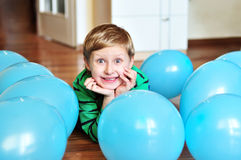 Boy laying with balloons royalty free stock photos