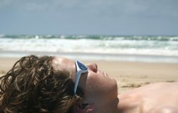 Boy laying on the beach. A young boy laying on the beach royalty free stock photography