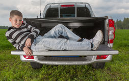 Boy laying on car trunk. On natural background Royalty Free Stock Photos