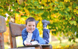 Boy laying down on a bench Royalty Free Stock Photos