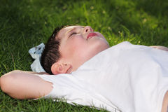 Boy laying down in grass Stock Photo