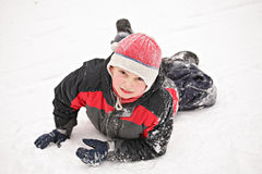 Boy laying down on snow Stock Photos