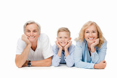 Grandparents. Boy laying on floor with grandparents isolated on white Royalty Free Stock Images