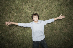 Boy laying on the grass Stock Photos