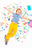 Boy laying in the middle of office supplies heap Stock Images