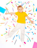 Boy laying among office supply objects collection Royalty Free Stock Photography