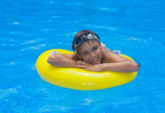 Boy laying on rubber ring in pool Stock Photography
