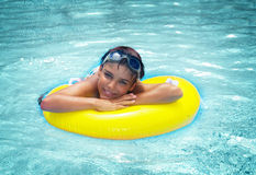 Boy laying on rubber ring in pool Royalty Free Stock Images