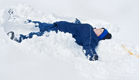 Boy laying in the snow Stock Photography