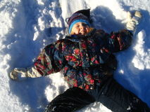 Girl Laying in Snow. Making a snow angel Stock Photo