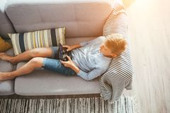 Boy laying on sofa plays with electronic devices - gamepad connected with smartphone stock photography