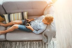 Boy laying on sofa plays with electronic devices - gamepad connected with smartphone stock image