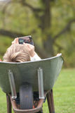 Boy Laying Wheelbarrow Using Mobile Phone Stock Photos