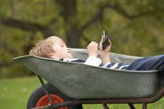 Boy Laying Wheelbarrow Using Smart Phone Royalty Free Stock Photo