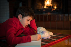 Boy laying and writing a letter to Santa Claus Stock Photos