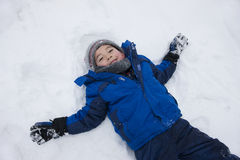 Boy lays down in snow. Royalty Free Stock Images