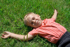 Boy Lays On The Grass Stock Photos