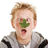 Boy with leaf on his nose. Teenage boy with a leaf on his nose making a funny cockeyed expression Royalty Free Stock Photos