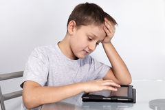 Boy leaned his head on the table on a Tablet PC Stock Photography