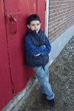 Boy leaning against door Stock Photography