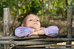 Boy Leaning on Arms on Top of Wooden Fence Stock Image