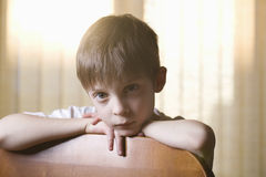 Boy Leaning On Back Of Chair Royalty Free Stock Photos