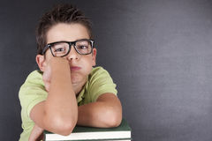 Boy leaning on boring attitude. Portrait of boy in school desk with a look of boredom and tiredness Stock Images