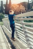 Boy leaning over a bridge railing looking down at river Royalty Free Stock Photography