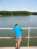 Boy leaning on railing by lake Royalty Free Stock Images