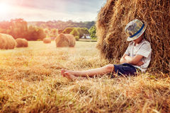 Boy leaning and sleeping against a haystack at sunset Stock Photo