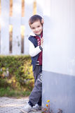 A boy leaning on a wall, smiling Stock Photography
