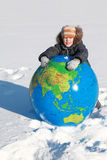 Boy leans on inflatable globe in winter Stock Photography