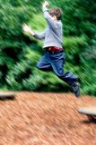 Boy leaps high in playground Stock Photography